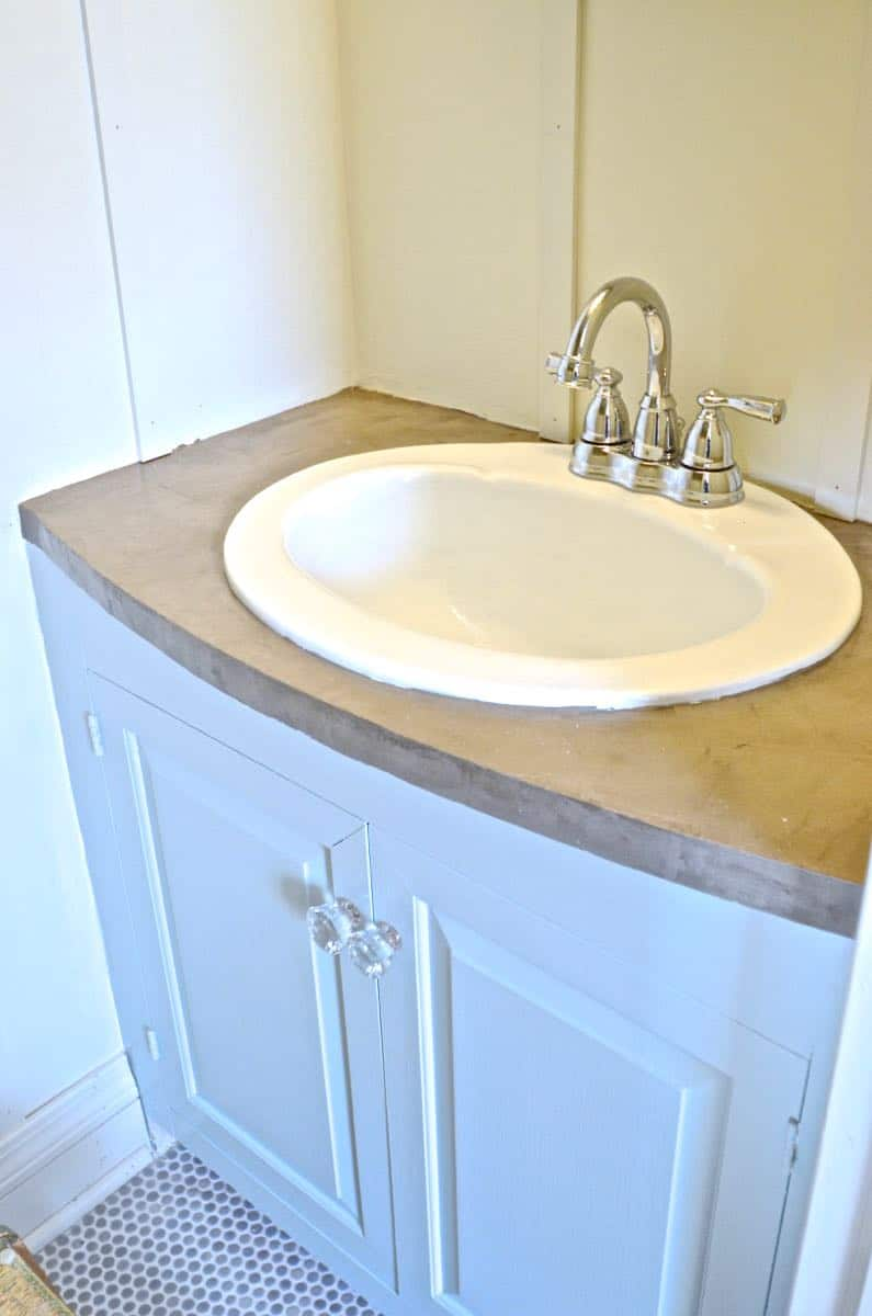 How to transform and old vanity top with concrete for a budget bathroom makeover.