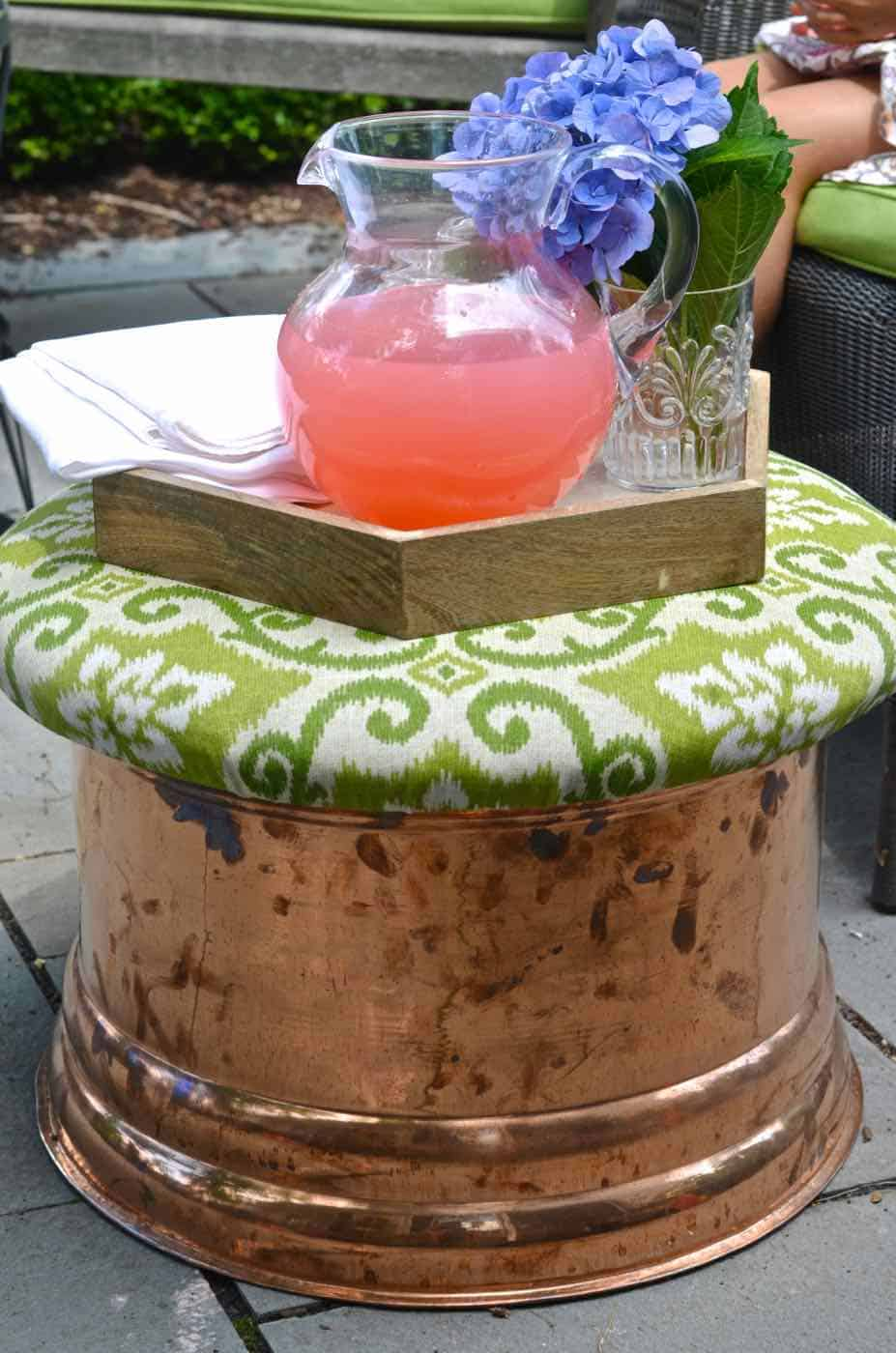 This copper garden hose cover got a makeover as an upholstered storage ottoman for our patio.