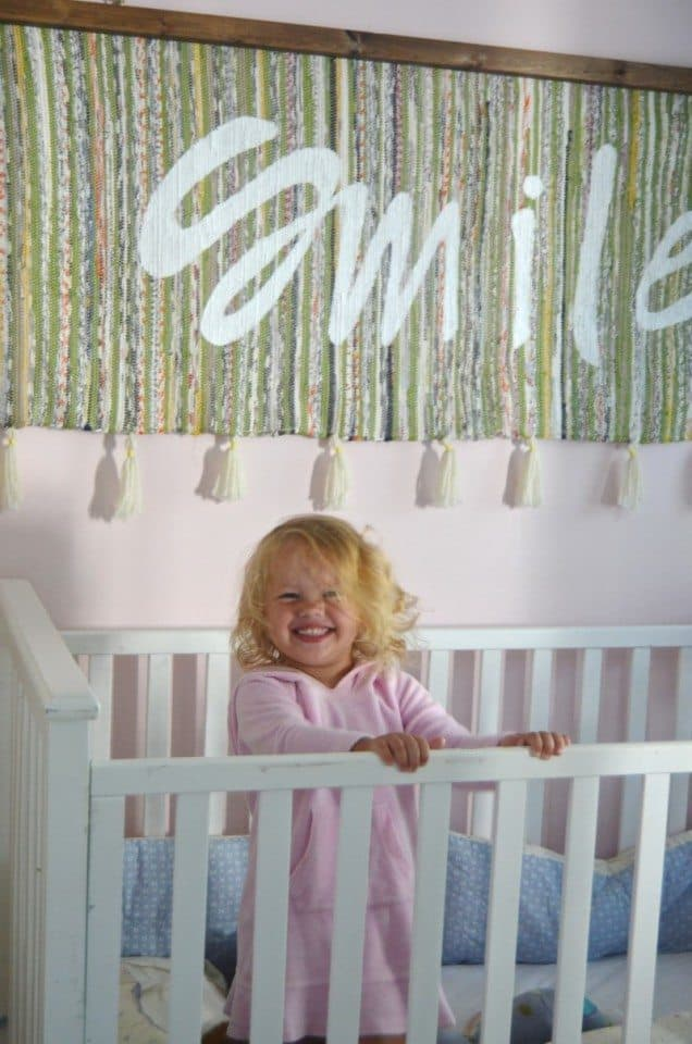 girl smiling in crib boho nursery