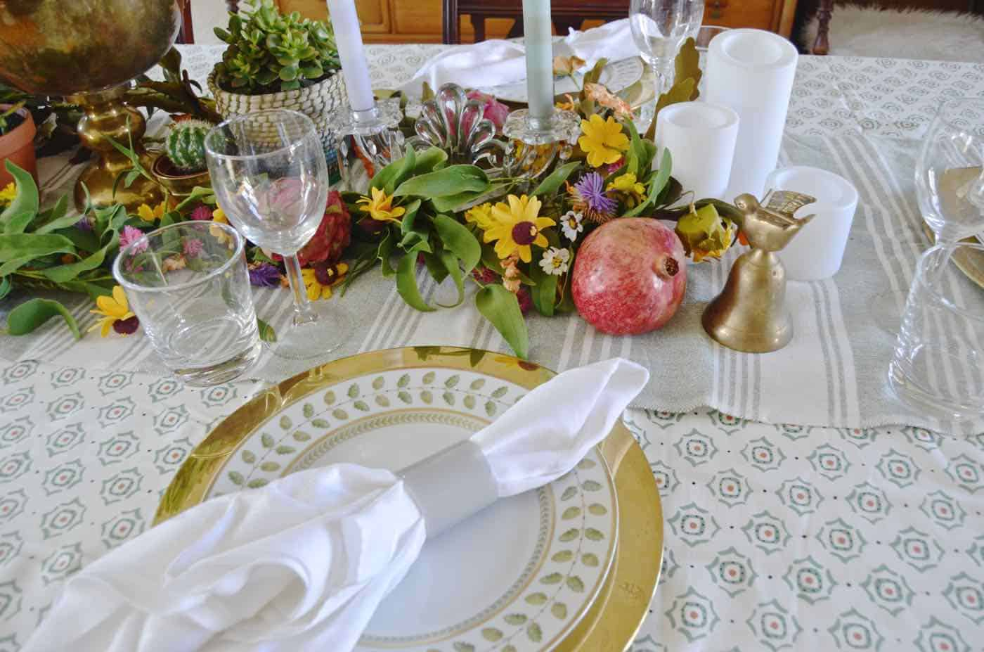 Thanksgiving tablescape with lush greenery and vegetables.