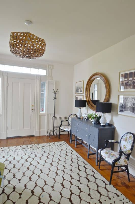 Eclectic foyer pulled together with refurbished furniture and fun fabric and accessories.