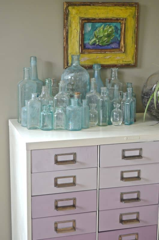 glass bottles on ombre file cabinet