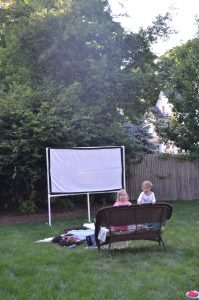 DIY backyard movie screen using PVC pipes and a clearance sheet.