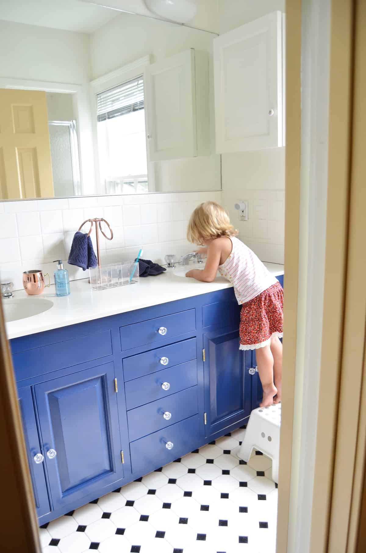 Repainting a basic white vanity with navy blue Satin Enamel paint for an easy bathroom makeover