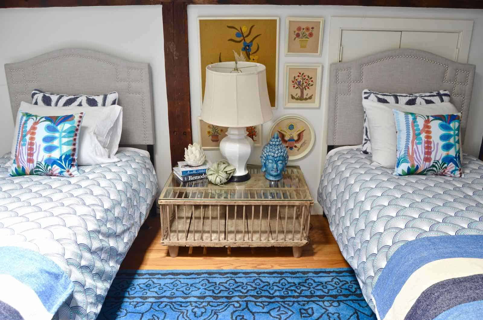 Updated guest room with new upholstered headboards and a repainted rich vintage gallery wall.