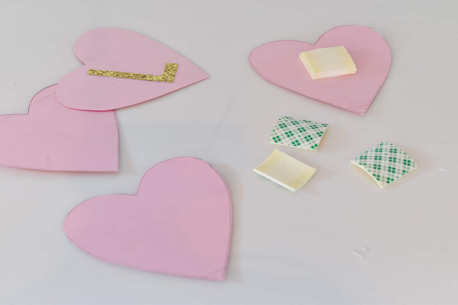 Add tape to the back of the hearts