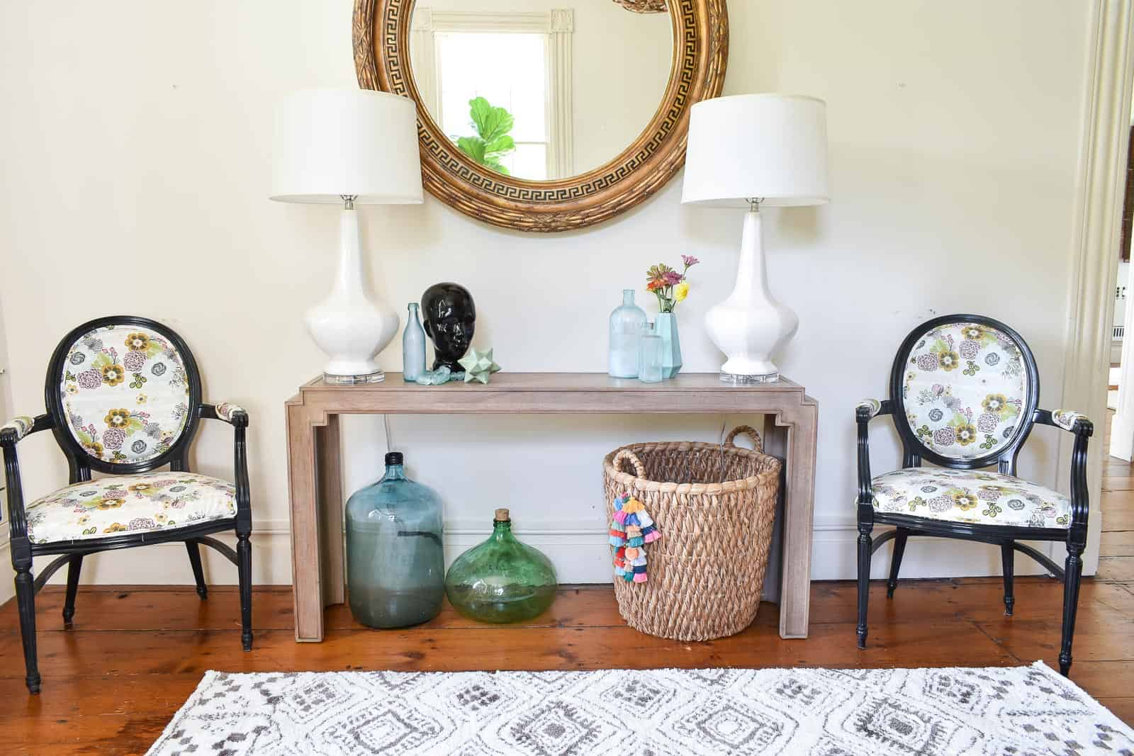 Bassett console table under round antique mirror