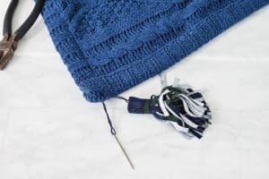 sew the tassel onto the blanket with embroidery thread