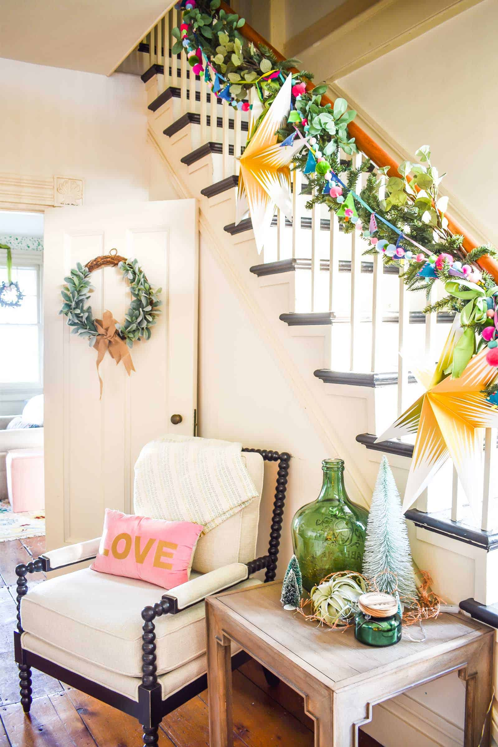 staircase with colorful garland and greenery