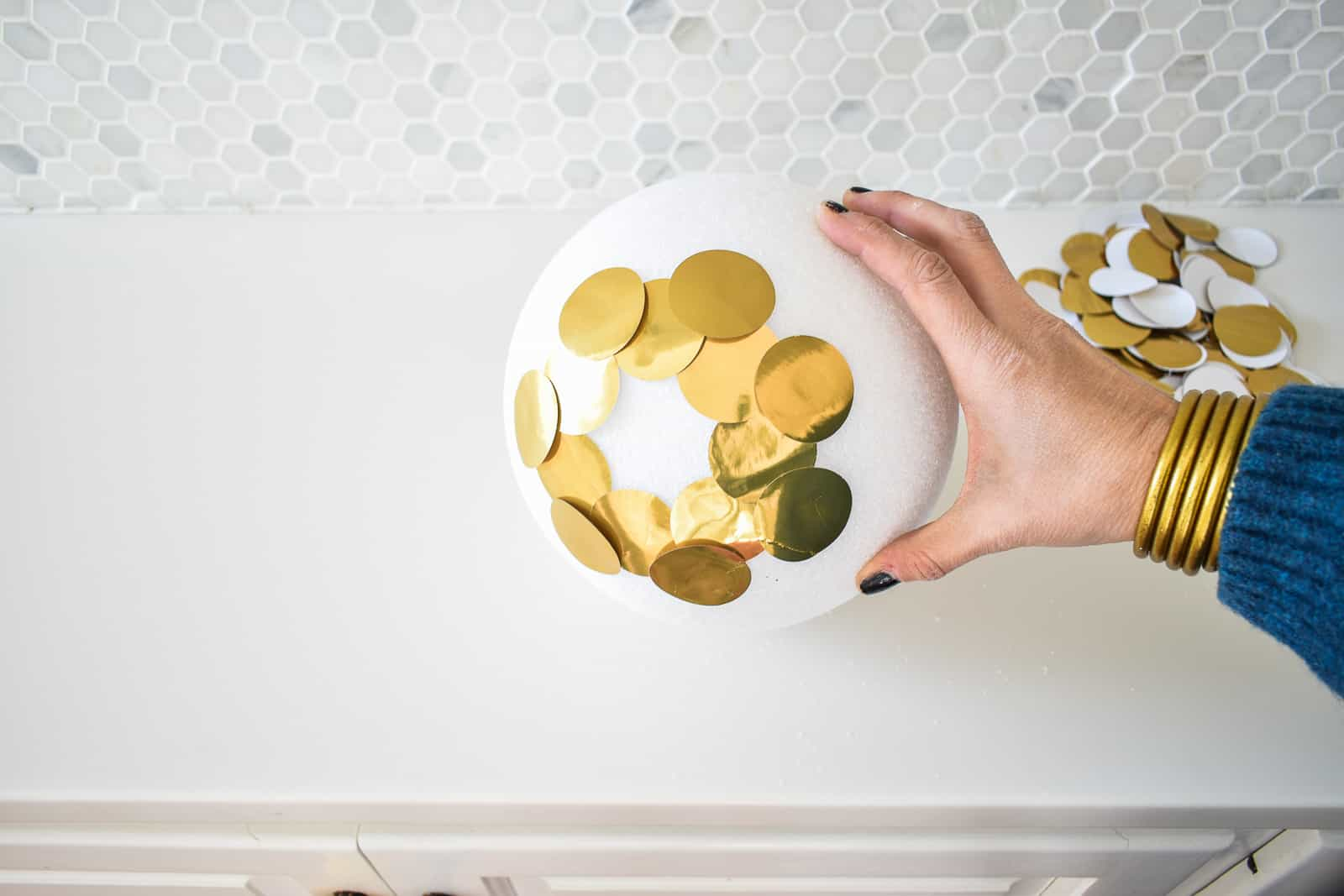glue gold circles onto foam ball