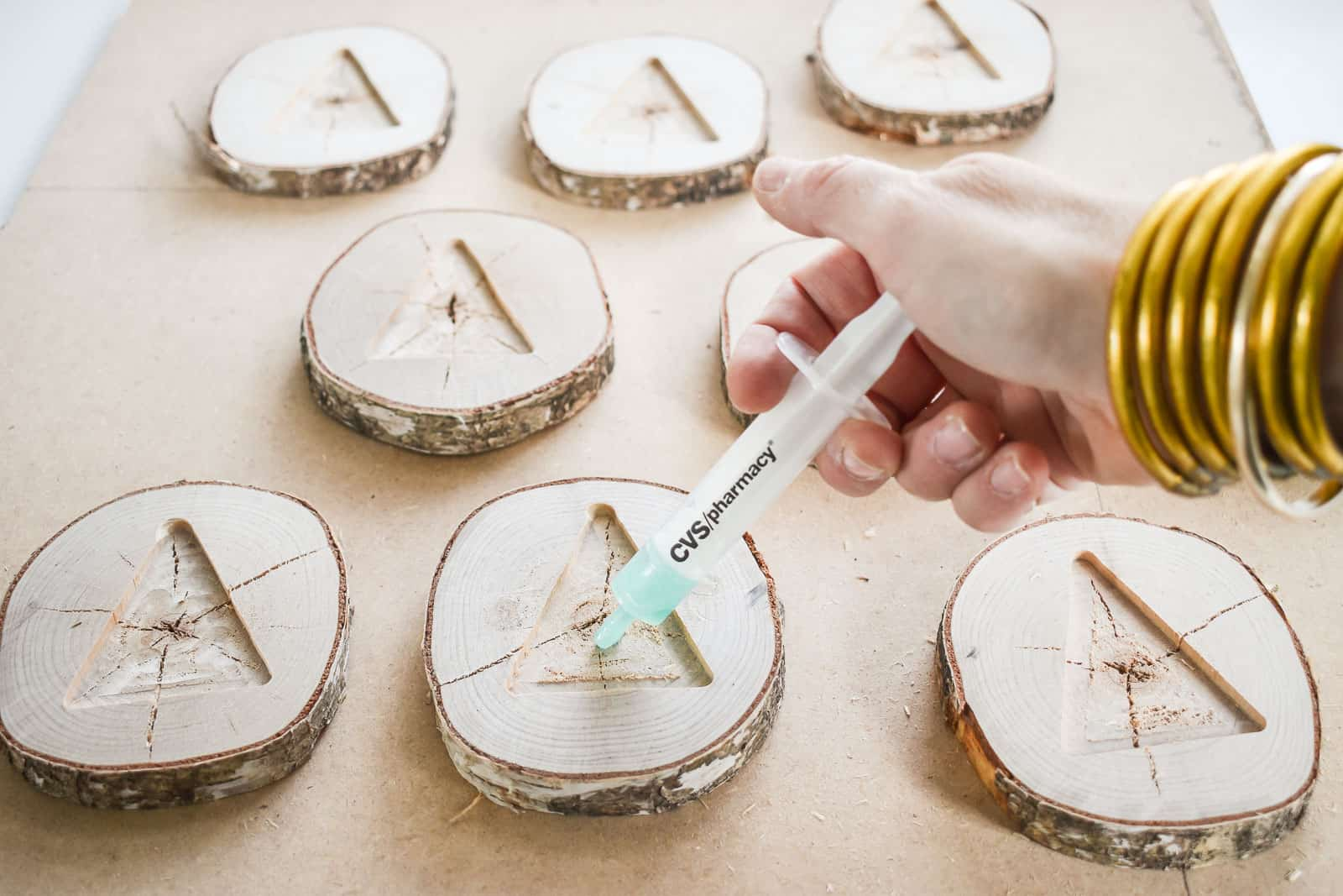 using a syringe to control the resin pour into the wood slices