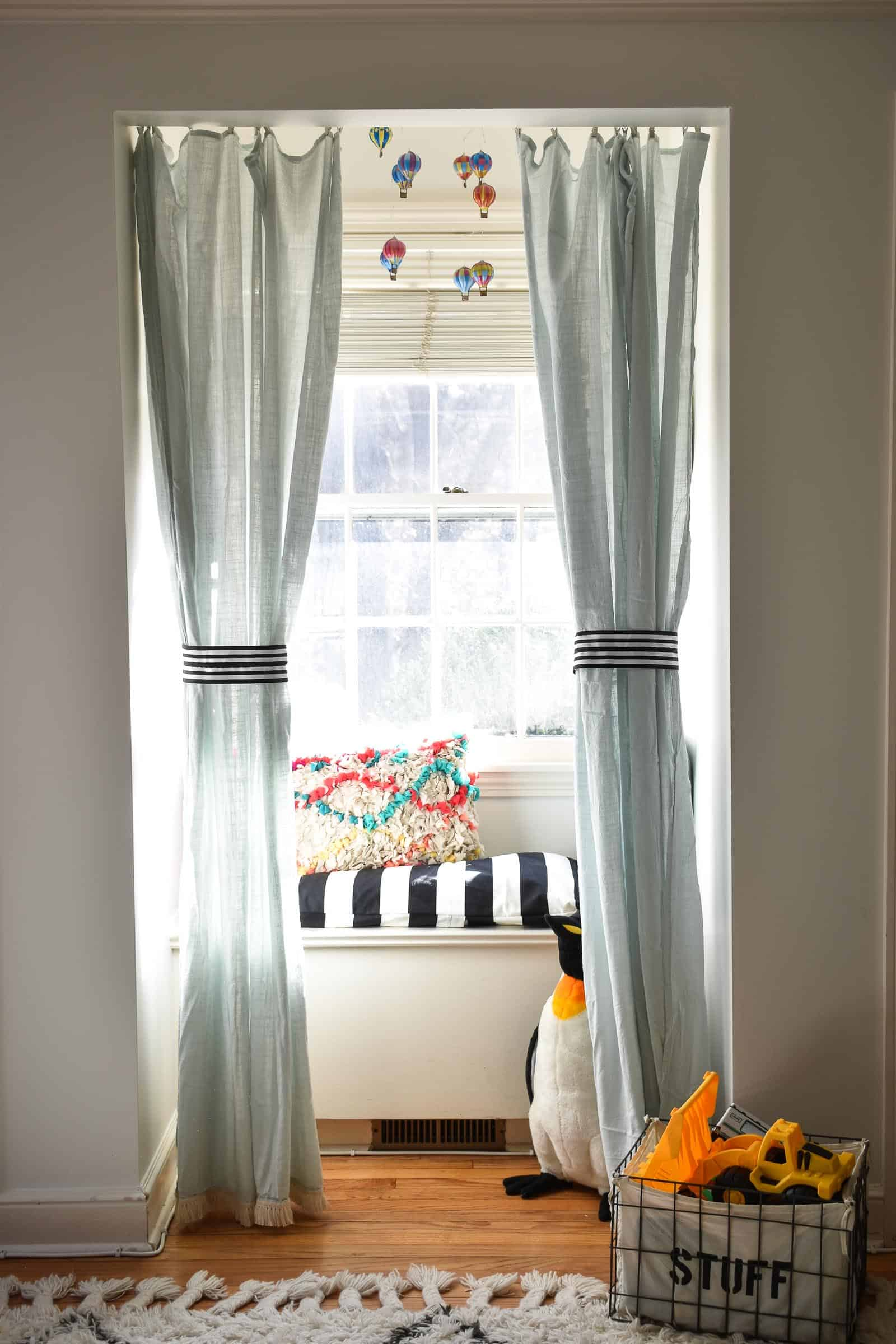 adding curtains to make a window seat reading nook