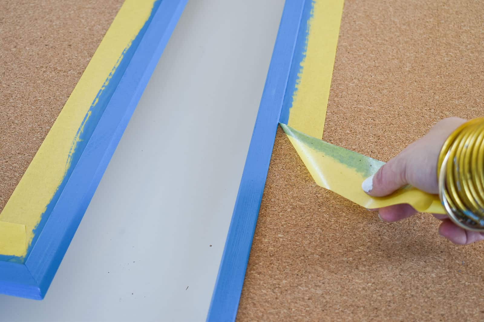painting a frame on a cork board