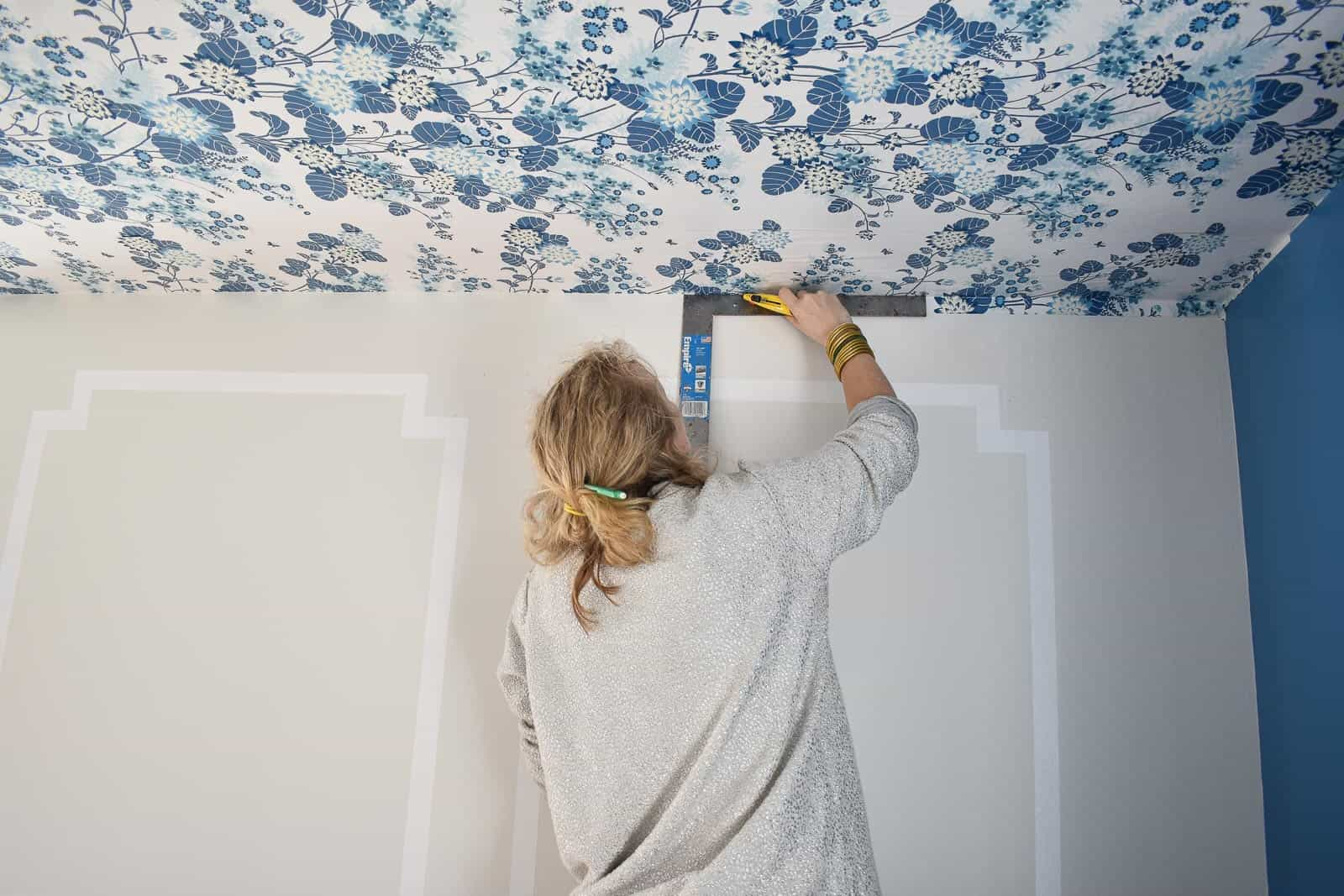 use a straight edge to cut the wallpaper at the corner