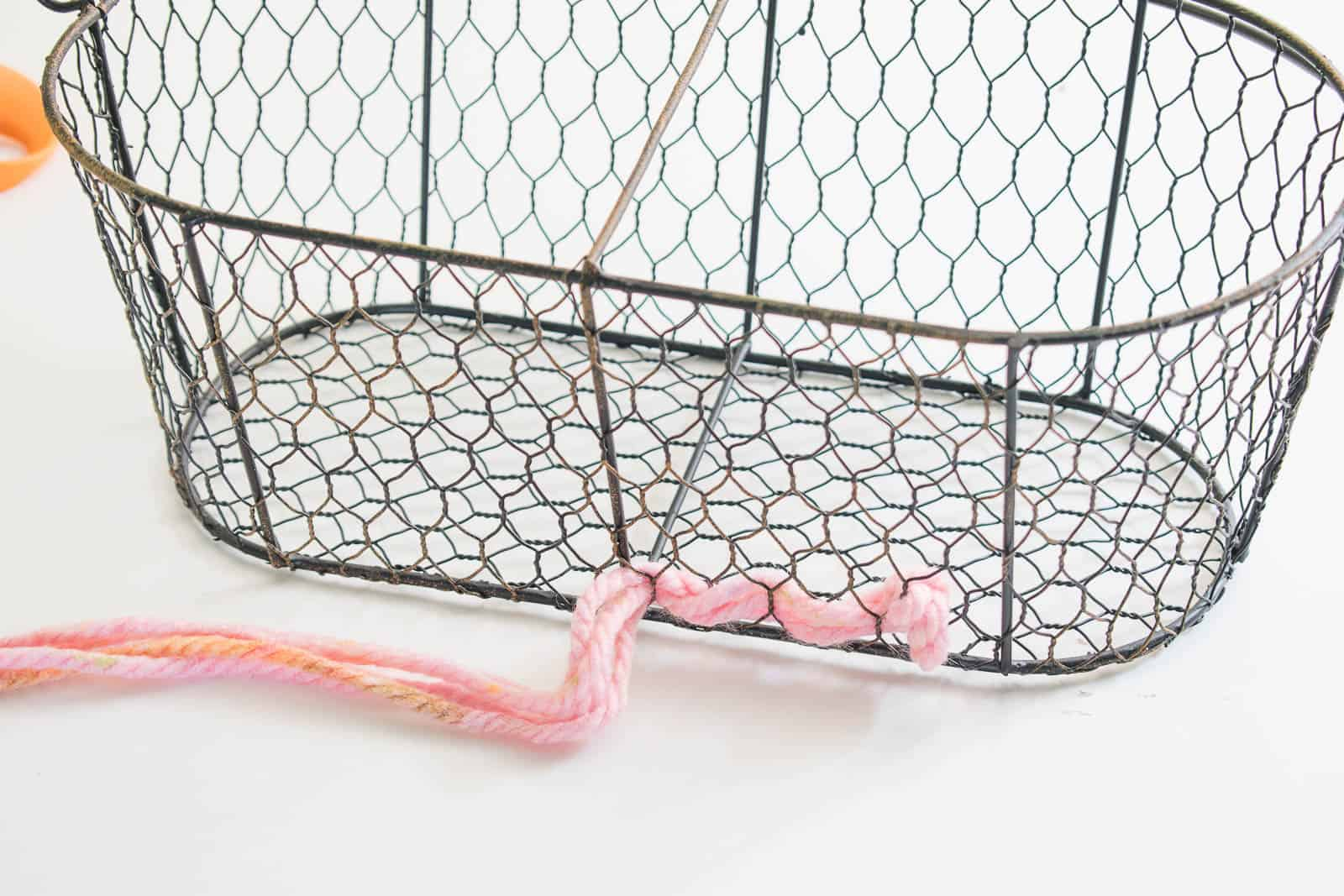 weave the yarn through the spaces of the basket