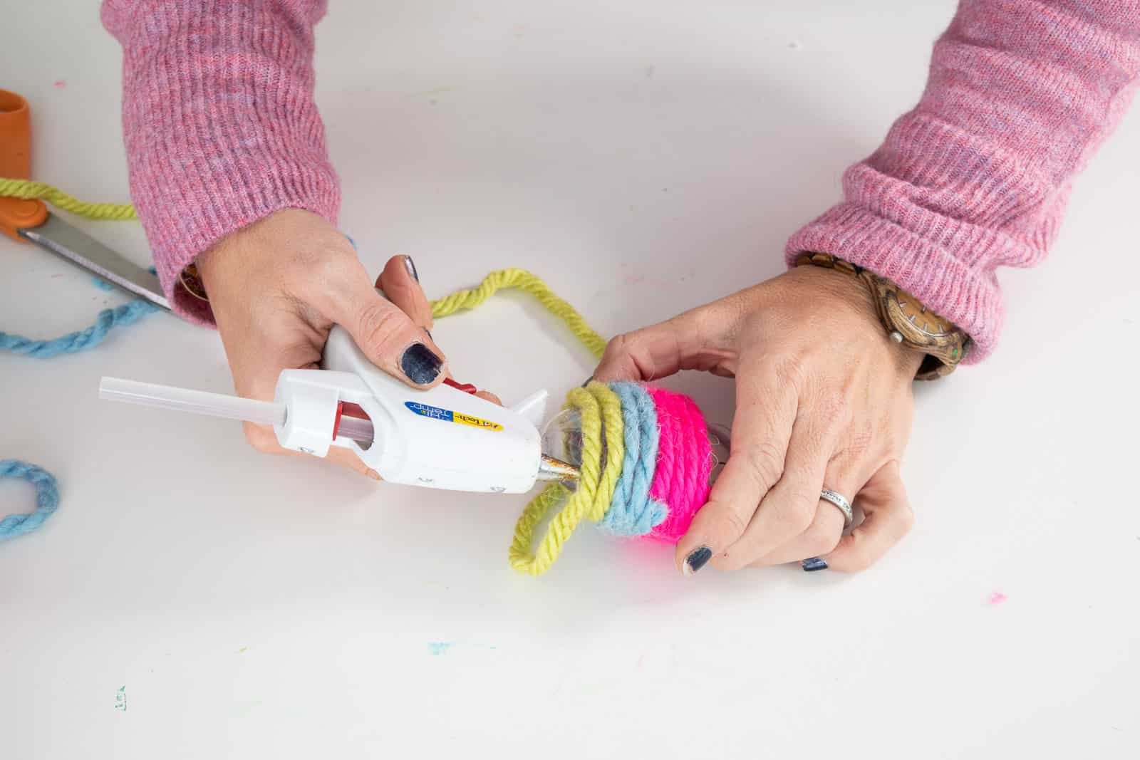 use the tip of the hot glue gun to help