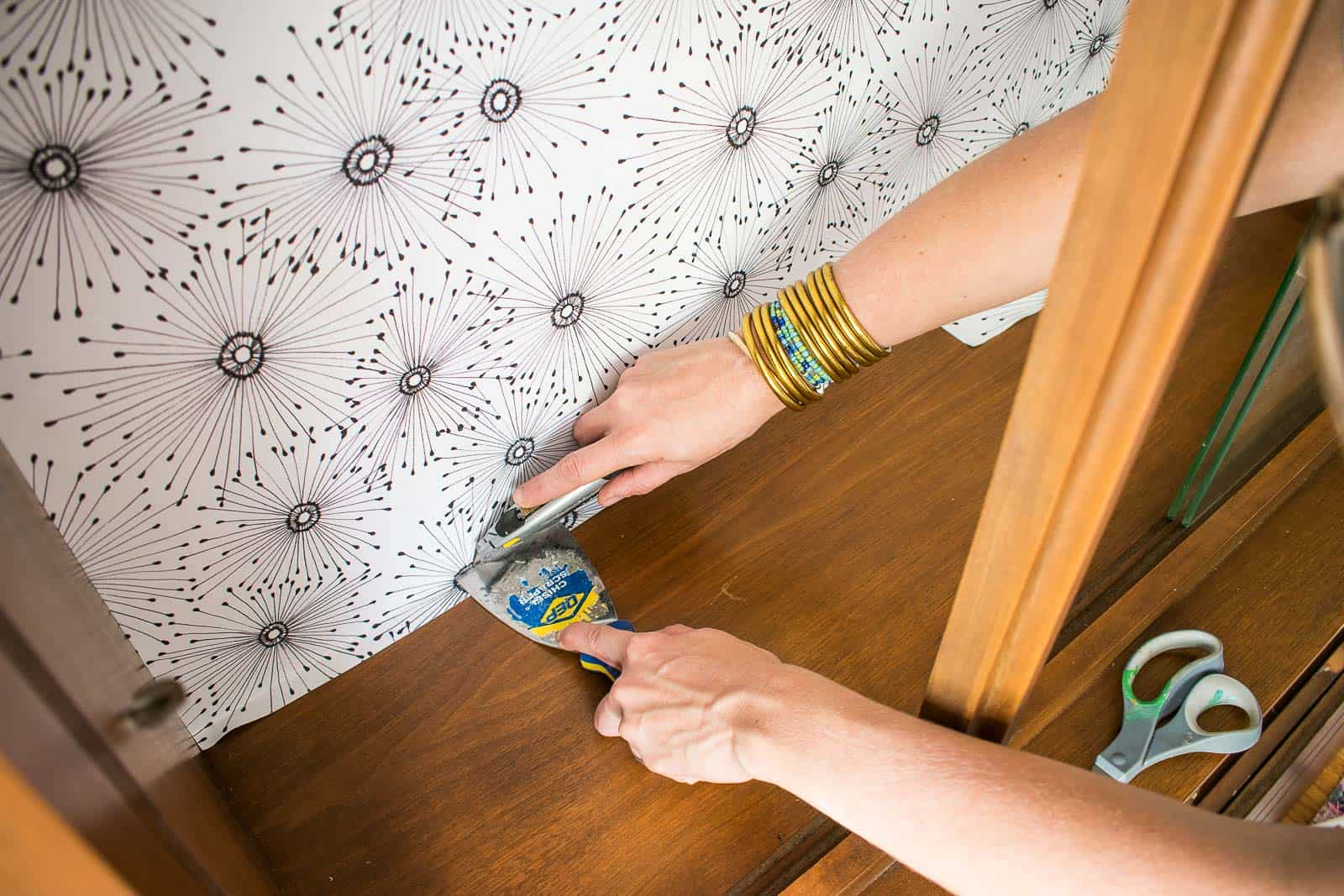 use a straight edge to trim excess wallpaper