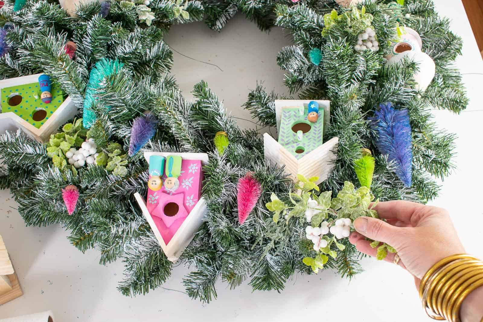 add holiday picks to wreath
