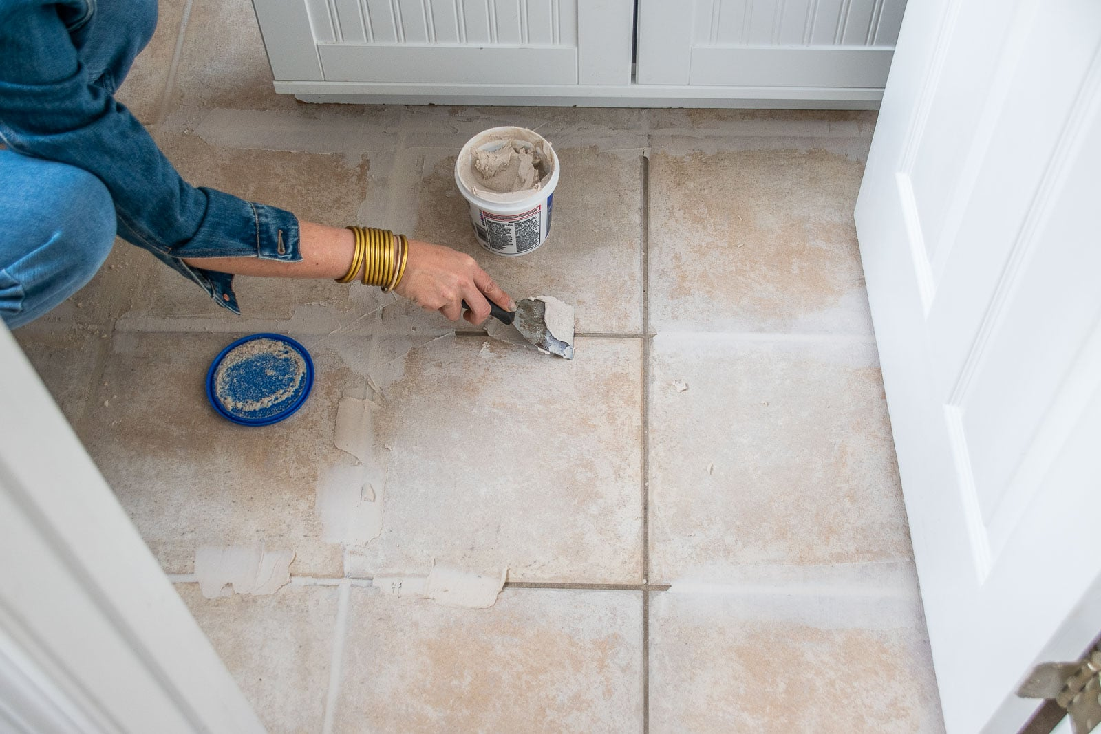 filling the grout on tile floors